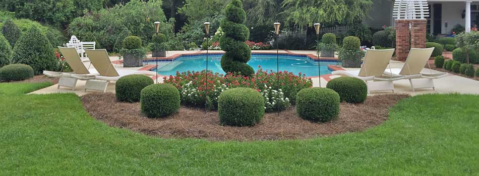 Mowing and landscape maintenance around a pool with beautifully trimmed shrubs in Wrens, GA.